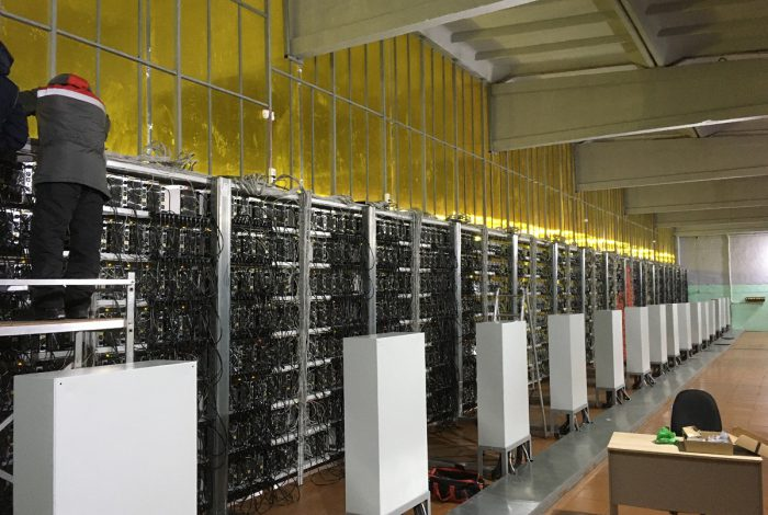 Фото техподдержка устанавливает S17pro на верхнюю полку майнинг-отель Cryptoreactor